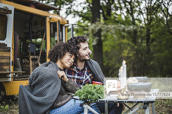 Junges multiethnisches Paar in eine Decke gewickelt  während es am Tisch sitzt und wegschaut