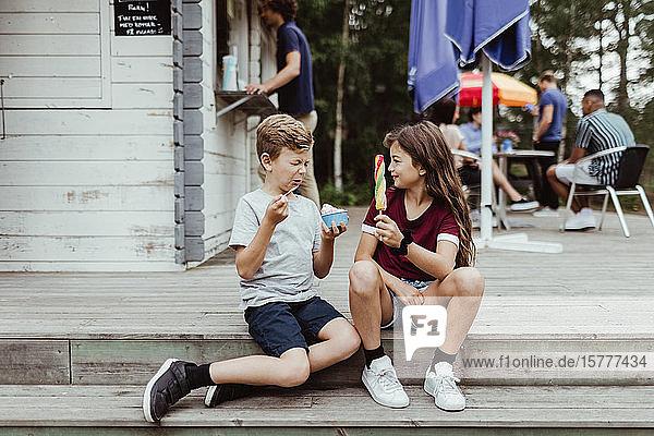 Brüder und Schwestern in voller Länge  die auf Holzstufen sitzend süße Speisen essen