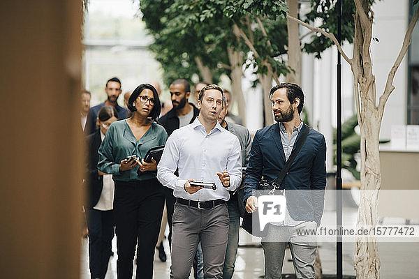 Unternehmer und Unternehmerinnen gehen vor dem Büro