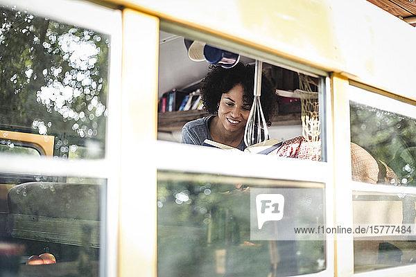 Junge Afro-Frau liest Buch  während sie im Wohnmobil liegt und durch ein Fenster gesehen wird