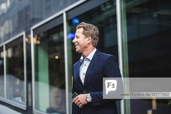 Smiling mature businessman with smart phone looking away while standing against office building