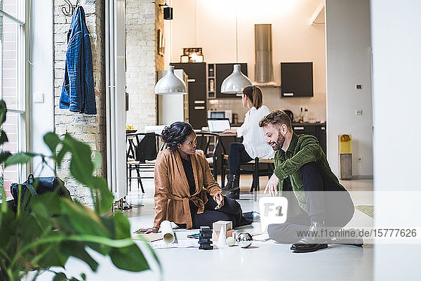 Smiling architects discussing while female entrepreneur working in background at home office