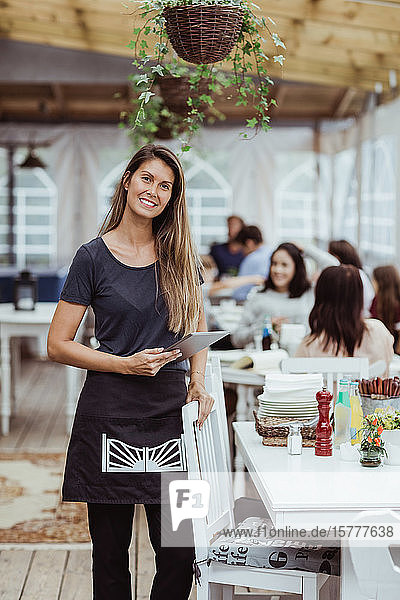 Portrait of smiling female owner holding digital tablet standing in restaurant