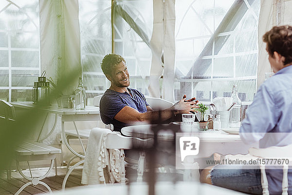 Smiling man talking with male friend while sitting in restaurant