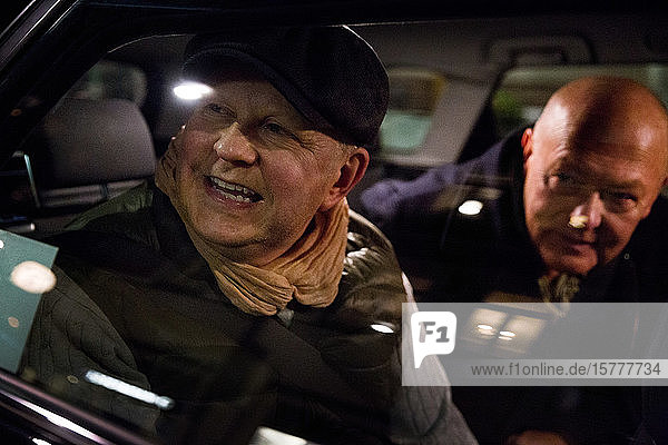 Smiling gay couple looking through window while sitting in car at night