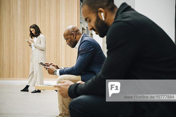 Male and female entrepreneurs using smart phone outside office