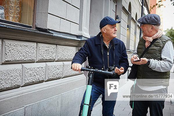 Älteres schwules Ehepaar benutzt Roller  während es in der Stadt sein Handy in der Hand hält