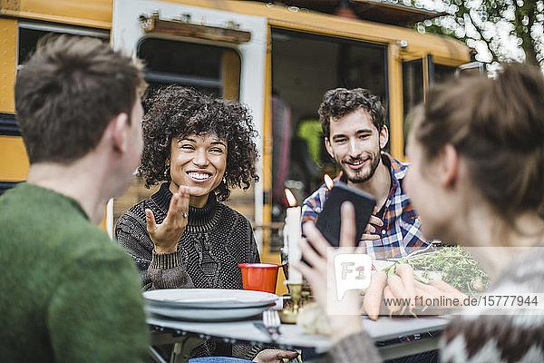 Lächelnde Frau zeigt Freunden  die am Tisch gegen den Wohnwagen sitzen  ihr Handy