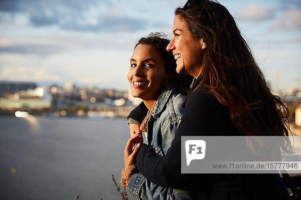 Lächelndes lesbisches Paar steht am Fluss in der Stadt gegen den Himmel