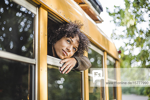 Thoughtful young woman looking through camper vehicle window during camping in forest