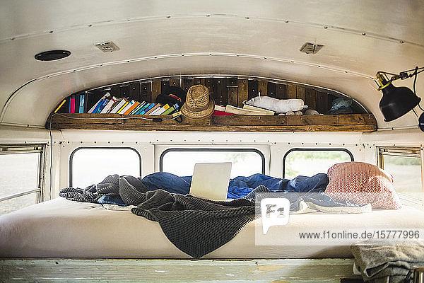Laptop und zerknautschte Decke auf dem Bett im Wohnmobil