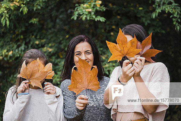 Mother and daughters hiding behind autumn leaves