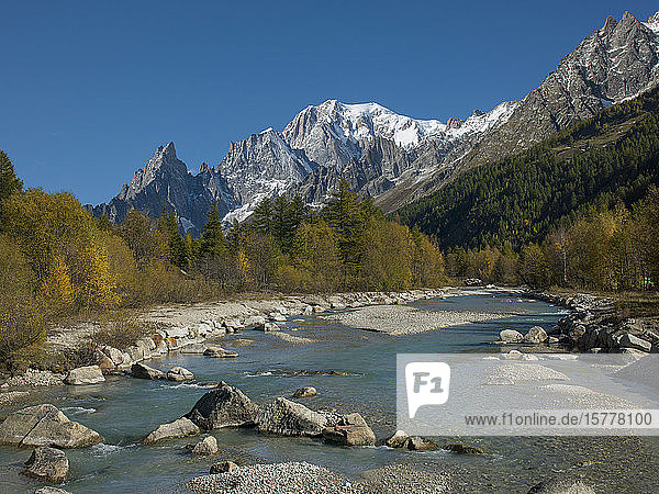 Snowcapped mountain by river in Aosta Valley  Italy