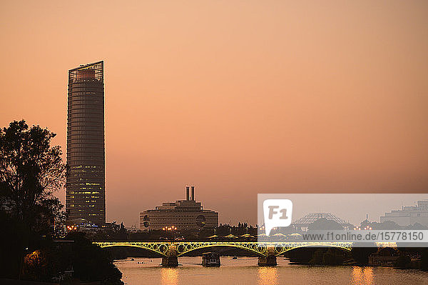 Triana Bridge in front of Sevilla Tower at sunset in Seville  Spain