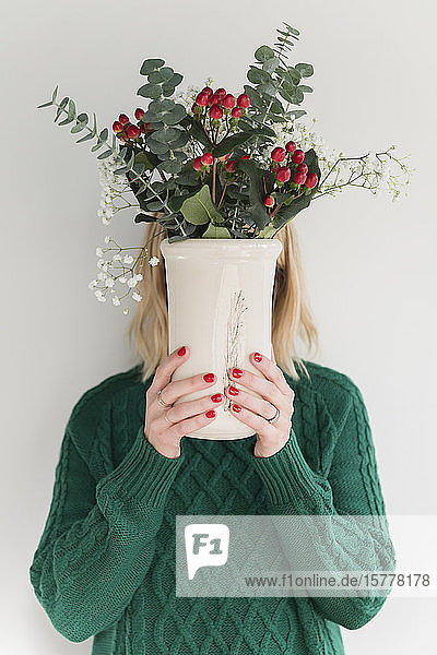 Woman wearing green holding vase of flowers