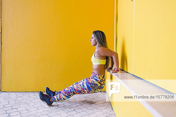 Woman doing wall sit by yellow wall