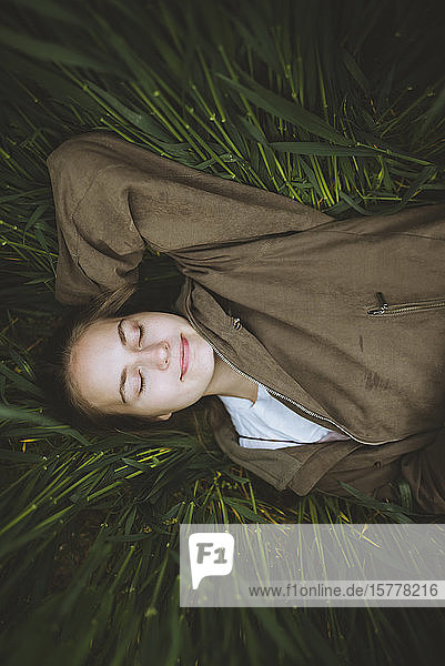 Smiling woman lying down in grass