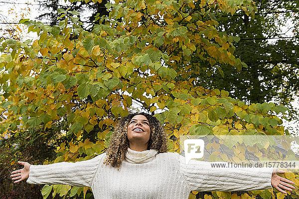 Lächelnde Frau mit ausgestreckten Armen an einem Baum