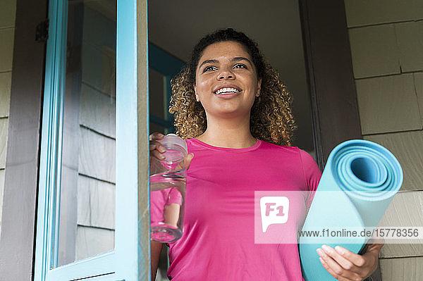 Lächelnde Frau mit Trinkflasche und Yogamatte