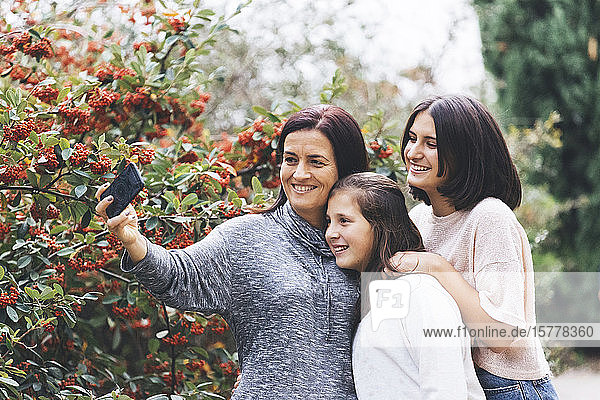 Mother and daughters smiling and taking selfie