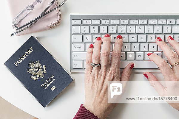 Woman typing on keyboard by passport