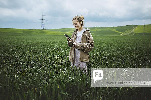 Smiling woman holding phone in field in Crimea  Ukraine