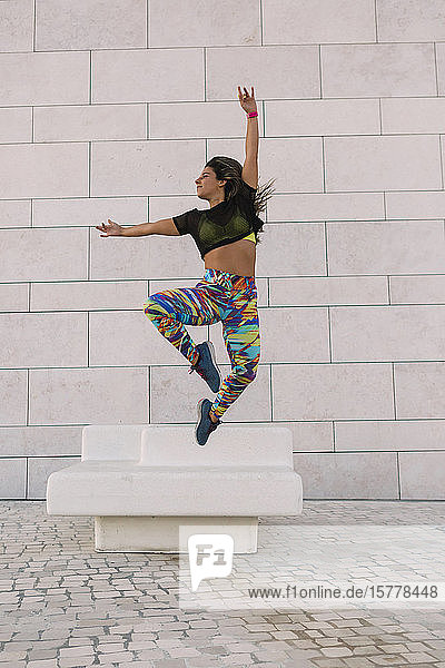 Woman jumping by wall