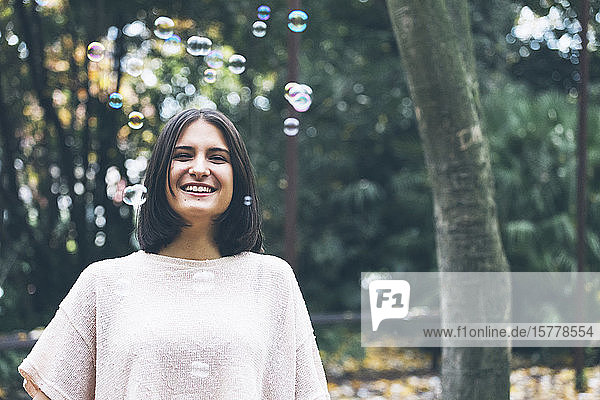 Smiling teenage girl under bubbles