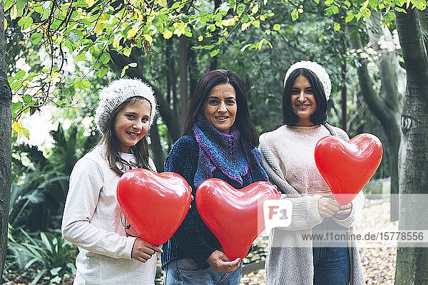 Mother and daughters holding heart balloons by trees