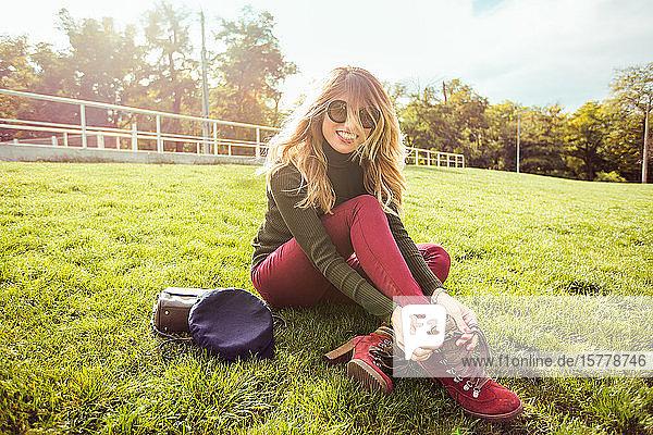 Porträt einer blonden Frau mit Sonnenbrille  die im Gras sitzt und lächelnd in die Kamera schaut