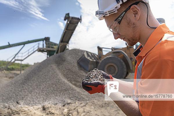 Arbeiter kontrolliert eine Handvoll abgesiebten Beton in einer Betonrecyclinganlage