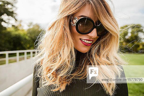 Porträt einer blondhaarigen Frau mit Sonnenbrille  die lächelnd wegschaut