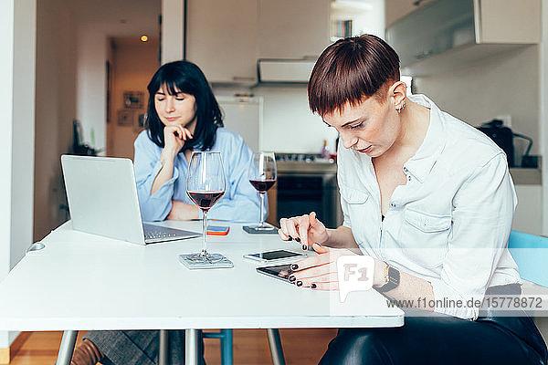 Frauen  die mit Laptop und digitalem Tablett am Tisch sitzen