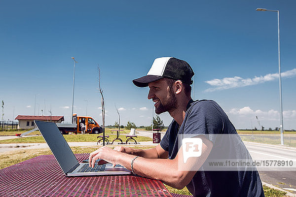 Mann mit Baseballmütze sitzt am Picknicktisch am Straßenrand und tippt am Laptop