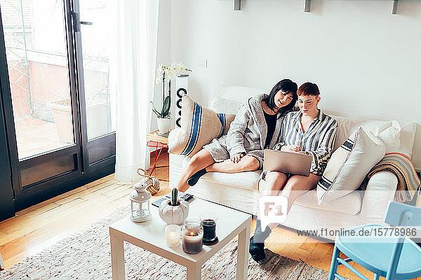 Women relaxing on sofa using laptop