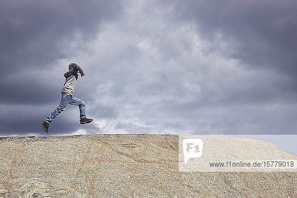Boy running on top of rock against stormy cloud sky