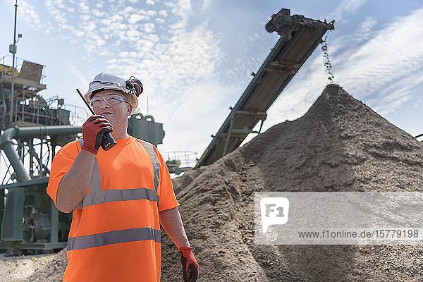 Arbeiter spricht über Walkie-Talkie mit Brecher und Betonsiebmaschine in einer Betonrecyclinganlage