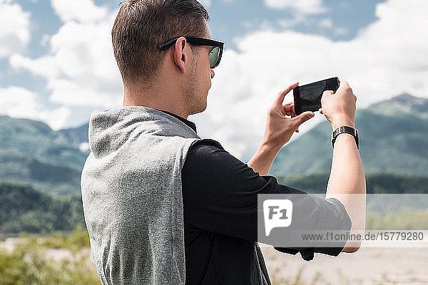 Männlicher Tourist beim Fotografieren eines Bergflusses mit einem Smartphone  Francenigo  Venetien  Italien