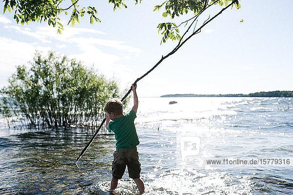 Junge erforscht Wasser mit dem Stock  Kingston  Kanada