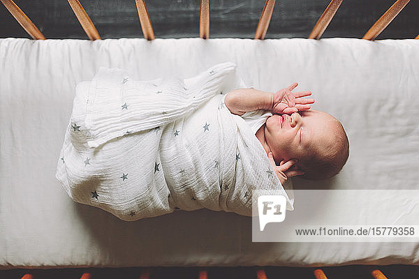 New born baby boy swaddled in cot  overhead view