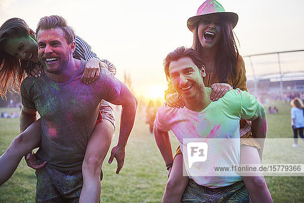 Two young couples covered in coloured chalk powder piggybacking at Holi Festival