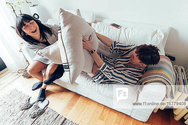 Kissenschlachten von Frauen auf dem Sofa  Hochwinkelansicht