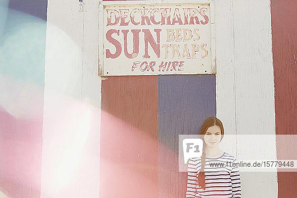 Girl beside deck chair rental hut