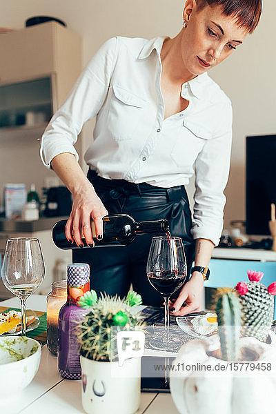 Frau schenkt Flasche Wein ein