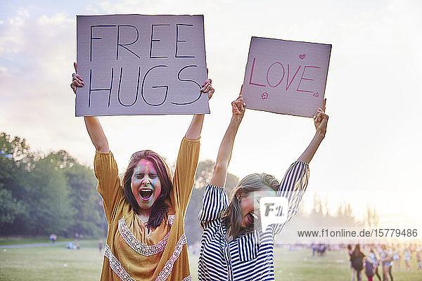Junge Frauen  die beim Holi-Festival tanzen und Zeichen der Liebe und freien Umarmung hochhalten