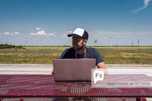Mann mit Baseballmütze sitzt mit Laptop am Picknicktisch am Straßenrand