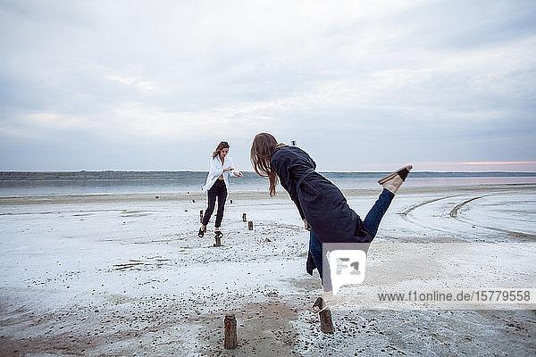 Frauen balancieren auf Holzstümpfen am Strand  Odessa  Ukraine
