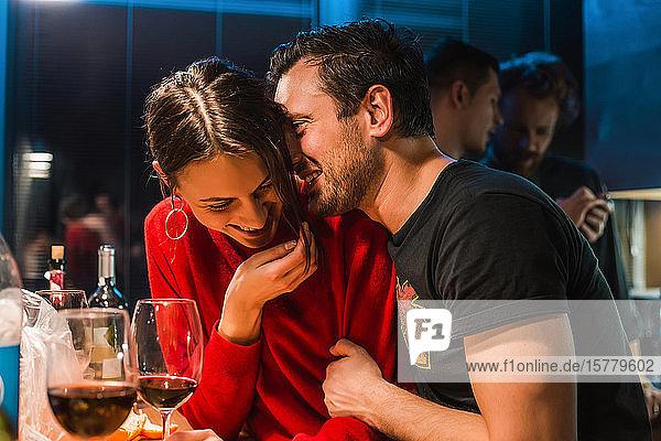Paar trinkt Wein auf einer Party in der Wohnung