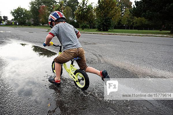 Junge fährt Fahrrad auf nasser Straße