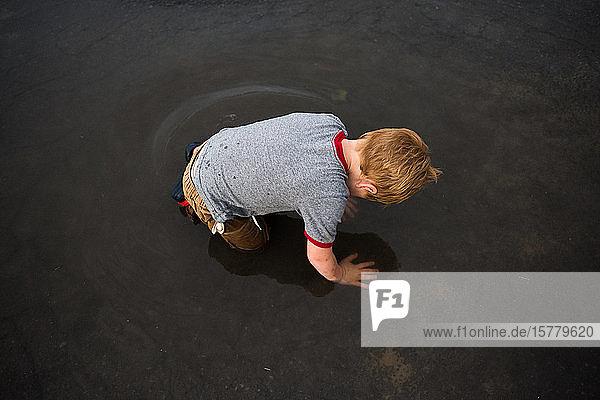 Junge kniend in Pfütze auf Straße